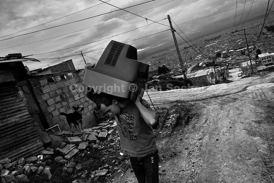 A displaced man carries a used TV on his shoulder in the slum of Ciudad Bolívar, Bogota, Colombia, 31 May 2010. With nearly fifty years of armed conflict, Colombia has the highest number of civil war refugees in the world. During the last ten years of the civil war more than 3 million people have been forced to abandon their lands and to leave their homes due to the violence. Internally displaced people (IDPs) come from remote rural areas, where most of the clashes between leftist guerrillas FARC-ELN, right-wing paramilitary groups and government forces takes place. Displaced persons flee in a hurry, carrying just personal belongings, and thus they inevitably end up in large slums of the big cities, with no hope for the future.