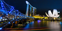 Pedestrian helix bridge lit up at night with the iconic Museum of Arts and Science and Marina Bay Sand hotel in the background, Singapore