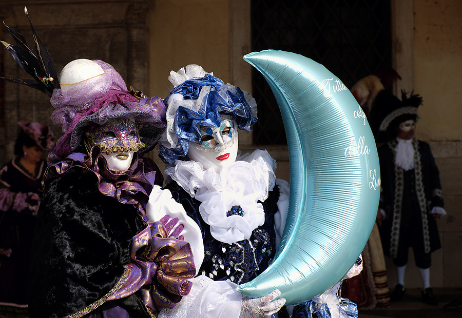 Woman dressed in traditional costume for Venice Carnival holding moon balloon standing at Doge's Palace, Piazza San Marco, Venice, Veneto, Italy