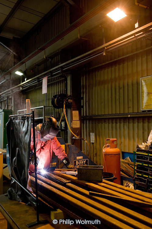 A welder works on a rail in the Points and Crossings Shed of London Underground's  Lillie Road Depot.  The depot produces replacement track for the tube network and offers a same day service for 'urgencies and emergencies'.  The depot is now run by London Underground following the collapse of PPP contractor Metronet in 2007.