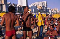 Young men enjoy Ipanema beach, Rio de Janeiro lifestyle, Brazil.