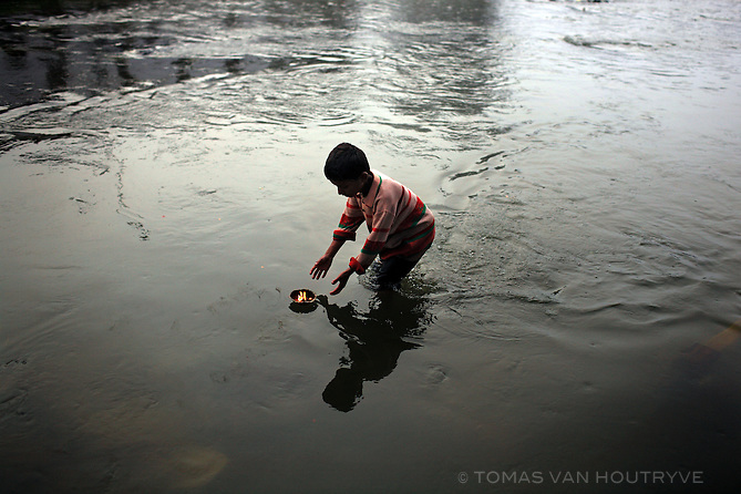 A boy wades in the Bagmati river to catch offerings floating down the river at the Pasupatinath Hindu temple in Kathmandu, Nepal on 18 October, 2007. Devotees place flowers, candles and coins into tiny boats made from leaves and send them down the river as offerings for Hindu gods. This boy was interested in pocketing the coins.