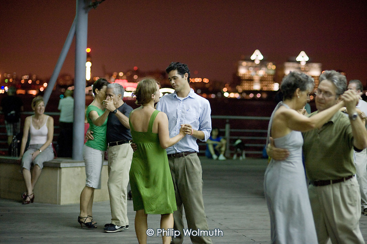 Night-time dancers and onlookers on a pier in West Village district of Manhattan, New York, overlooking the Hudson River and New Jersey river bank.
