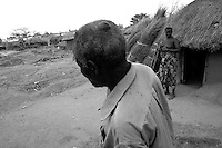 Beaten by the LordÕs Resistance Army, this man still has the scars from his aggressors. His wife looks on from their hut located in the Unyama Internally Displaced PeopleÕs (IDPs) camp. The war in Northern Uganda began in 1986 between the LordÕs Resistance Army (LRA) and the Ugandan PeopleÕs Defense Forces (UPDF). The LRA has reigned terror and carnage on Northern Uganda and Southern Sudan ever since. The rebels commonly abduct children to fuel their personnel needs and quickly turn them into soldiers, porters and sexual slaves. The ongoing war has significantly damaged the region and has left an ongoing burden on the local population. Unyama (off Kitgum Road North) Gulu District, Uganda, Africa. December 2005 © Stephen Blake Farrington