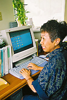 Asian woman working on computer in office setting