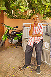 Marrakesh, Morocco. Candid portrait of man sitting on truck bed.