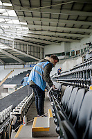 SWANSEA, WALES - MAY 17: A Cleaner Cleans seats at the Liberty Stadium prior to the Premier League match between Swansea City and Manchester City at The Liberty Stadium on May 17, 2015 in Swansea, Wales.  (photo by Athena Pictures)