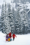 Family having fun in new snow while sledding, Rocky Mtns, CO