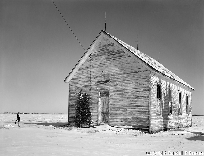 """""""Prairie View School"""" <br /> Illinois<br /> <br /> I was driving in rural Fayette County, Illinois during the Christmas holidays when I happened upon this abandoned schoolhouse sitting at the edge of a frozen field. The wood sign hanging above the door read, """"Prairie View School, Dist. No. 112."""" It was built in the 1880's and served well past the turn of the century. The conifer tree standing beside the door looks like it was decorated with snow for the holidays and shadows on the side of the building indicate that a big shade tree stands nearby. Little color was present in the scene so it was well suited for black and white photography."""