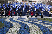 Pictured: People take pictures of the Greek flag shaped flower bed in Syntagma Square, Athens, Greece. Wednesday 24 March 2021<br /> Re: Preparations are under way to celebrate the 200 anniversary from the beginning of the Greek revolution of 1821, after an almost 400 year rule by the Ottoman empire, Athens, Greece.