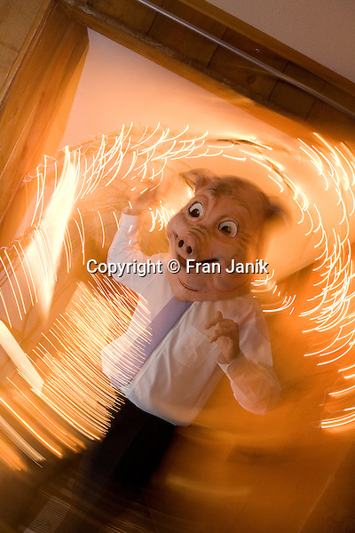 A swirl of bright lights encompasses a well dressed man wearing a pig head as he dances during a wedding reception.