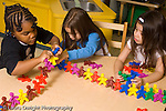 Education preschoool children ages 3-5 trhee girls playing with manipulatives connecting colorful pieces horizontal