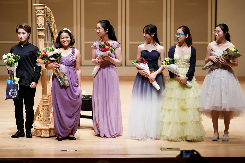 Performers stand on stage after the Stars of Tomorrow Concert at the 11th USA International Harp Competition at Indiana University in Bloomington, Indiana on Thursday, July 11, 2019. Pictured from left are: Xinyue Zhang, Renee Murphy, Hanjiao Zou, Yuet Kan, Annette Lee and Valerie Sim. (Photo by James Brosher)