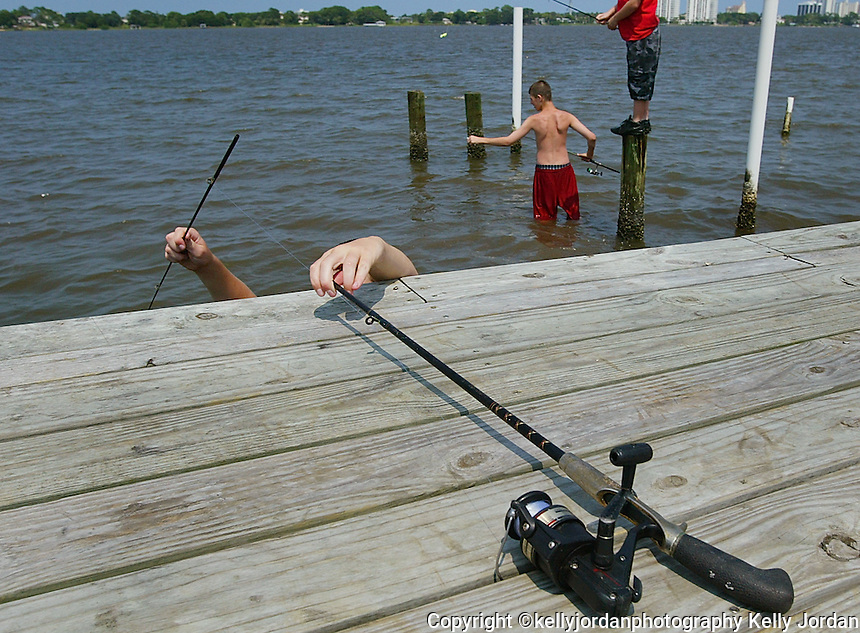 """Hands appear eerily over the edge of a dock along Riverside Drive in Holly Hill, foreground, as Chris Powers, 14, [cq] reaches over to grab his pole so he can head out to a group of pilings to fish with his brother Jonathan Powers, 11, [cq] right, and his friend John Valderrama, 14, [cq] middle as the group spends their afternoon fishing Monday July 12, 2004. The trio enjoys fishing and do it as oftern as they can. Monday there was a catch, so to speak. Chris and his brother Jonathan had to clean their room in order to gain the privaledge of the outing. """"This morning we had to clean our room, it was horrible, but we got to come fishing this afternoon"""", said Chris as he explained how usually they can fish if their chores are done for the day.(Kelly Jordan)..**FOR STAND ALONE FEECH**"""