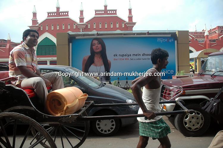 A rickshaw passes by a Billboard advertising the low rates for Reliance Mobile connection.  Kolkata, West Bengal,  India  7/18/2007.  Arindam Mukherjee/Landov