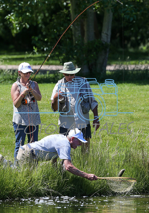 Dave Sorokwasz, right, and Marty Wright, with net, help as breast cancer survivor Michele Kimzey, of Placerville, reels in a fish during a Casting for Recovery retreat in Gardnerville, Nev., on Friday, June 30, 2017. The nationwide program, hosted locally with Carson Tahoe Cancer Center, pairs cancer survivors with fly-fishing guides.  <br /> Photo by Cathleen Allison/Nevada Photo Source