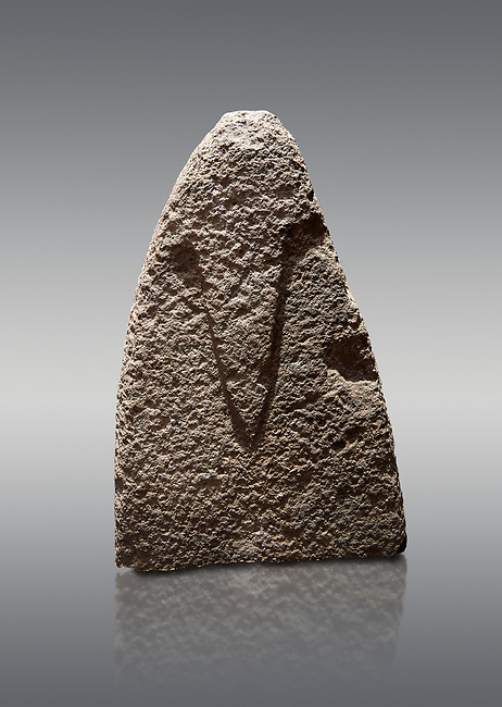 Top section of a Late European Neolithic prehistoric Menhir standing stone with carvings on its face side. The representation of a stylalised male figure starts at the top with a long nose from which 2 eyebrows arch around the top of the stone. Excavated from Amassed VII, Allai. Menhir Museum, Museo della Statuaria Prehistorica in Sardegna, Museum of Prehoistoric Sardinian Statues, Palazzo Aymerich, Laconi, Sardinia, Italy. Grey background.