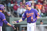 Shortstop Logan Davidson (8) of the Clemson Tigers is congratulated by Matt Williams after scoring a run in the Reedy River Rivalry game against the South Carolina Gamecocks on Saturday, March 3, 2018, at Fluor Field at the West End in Greenville, South Carolina. Clemson won, 5-1. (Tom Priddy/Four Seam Images)