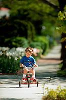 Yong boy riding a tricycle.