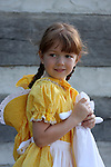 A young girl dressed in a prairie dress historical reenactment