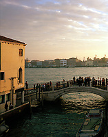 Tourists crowd onto a bridge over a canal in Venice as dusk descends, watching a cruise ship coming into anchor for the night.