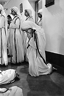 """Calcutta, India. April 04, 1975. Mother Teresa prays in the morning hours along with the other sisters as part of the """"Missionaries of Charity"""" Mother Teresa (Agnes Gonxha Boyaxihu) the Roman Catholic, Albanian nun revered as India's """"Saint of the Slums,"""" was awarded the 1979 Nobel Peace Prize."""
