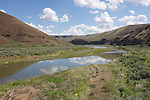 The blue sky and clouds reflect in the John Day River, Oregon.
