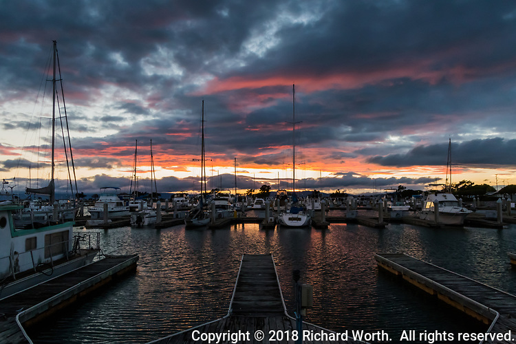 Rippling water in empty boatslips reflect the glowing sky overhead at the San Leandro Marina on San Francisco Bay.