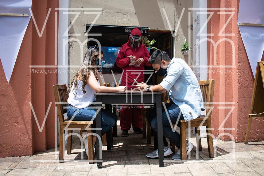 """BOGOTA - COLOMBIA, 05-09-2020: Un mesero toma el pedido de unos clientes durante el primer día del piloto de apertura de restaurantes y cafés al aire libre, denominado """"Bogotá a Cielo Abierto"""", en el Chorro de Quevedo en el centro de Bogotá que ahora tiene sus calles pintadas con formas geométricas en pintura neón y cuenta con mesas, distribuidas estratégicamente para mantener el distanciamiento físico al finalizar la cuarentena total en el territorio colombiano causada por la pandemia  del Coronavirus, COVID-19. / A waiter takes the order from the customers during the first day of the pilot for the opening of restaurants and outdoor cafes, called """"Bogotá a Cielo Abierto"""", in Chorro de Quevedo in the center of Bogotá, which now has its streets painted with geometric shapes in neon paint and has tables, strategically distributed to maintain physical distancing at the end of the total quarantine in the Colombian territory caused by the Coronavirus pandemic, COVID-19. Photo: VizzorImage / Johan Rugeles / Cont"""
