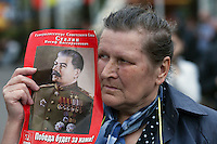 Moscow, Russia, 01/05/2010..A woman holds a portrait of Stalin at  an illegal demonstration in central Moscow. A variety of political groups took to the streets on the traditional Russian Mayday holiday.