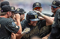Vanderbilt Commodores outfielder Stephen Scott (19) celebrates with his teammates after hitting a home run during the second inning of Game 8 of the NCAA College World Series against the Mississippi State Bulldogs on June 19, 2019 at TD Ameritrade Park in Omaha, Nebraska. Vanderbilt defeated Mississippi State 6-3. (Andrew Woolley/Four Seam Images)