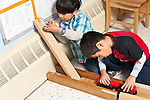 Education preschool 3-4 year olds two boys playing separately with ramp made from blocks and vehicles and toy train