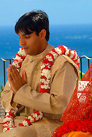 Tradditional Hindi wedding with groom wearing carnation flowers sitting in prayer