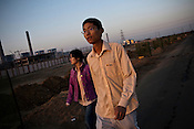 25 year old Chinese interpreter, Yuan Lei (right) with his girlfriend, Cui Yan (left) are seen going for work to the Adani Power plant in Mundra port industrial city of Gujarat, India. Indian power companies have handed out dozens of major contracts to Chinese firms since 2008. Adani Power Ltd have built elaborate Chinatowns to accommodate Chinese workers, complete with Chinese chefs, ping pong tables and Chinese television. Chinese companies now supply equipment for about 25% of the 80,000 megawatts in new capacity.