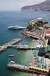 Holiday makers sun bake on floating sun beds on the Meditteranean sea at the main port of Sorrento town looking out towards Naples and Mt Vesuvius on the Amalfi Coast of Italy