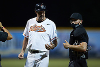 Burlington Sock Puppets head coach Jack McDowell chats with home plate umpire Garrett Griffin during the game against the Bluefield Ridge Runners at Burlington Athletic Park on June 8, 2021 in Burlington, North Carolina. (Brian Westerholt/Four Seam Images)