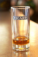 A glass of Ricard 45 pastis on a zinc bar in a cafe in Paris. Part of a series of photos showing that when you add ice and water the drink becomes cloudy milky Pastis is a spirit high alcohol drink flavoured flavored with herbs such as anise (badiane, anis étoilé etoile) and other spices. It is sometimes called pastis or Absinth absinthe. It is served in a tall glass with ice and you pour water on it. It gets cloudy milky when water is added. It is a favourite drink aperitif in Provence Southern France.