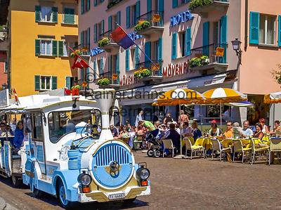 Schweiz, Tessin, Ascona am Lago Maggiore: auf der Promenade reihen sich Cafes und Restaurants aneinander - Start der Stadtrundfahrt mit dem Bummelzug | Switzerland, Ticino, Ascona at Lago Maggiore: cafes and restaurants at the promenade - start of sightseeing tour with the train
