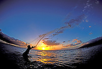Hawaiian man throws a net at sunset in Kihei, Maui.