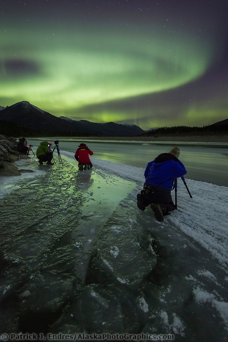 Photographers take pictures of the northern lights reflecting in the water of a river in Alaska's Arctic Brooks Range.