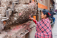 Nepal, Kathmandu.  Woman Praying for no Toothache at the Shrine to the Toothache God, Bangemudha Square.