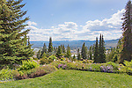 The city of Wenatchee as seen from the mountainside gardens of Ohme Gardens.  This is the confluence of the Columbia River on the left and the Wenatchee River on the right.  Fruit packing plants in the foreground.  Cascade Mountains in the background.