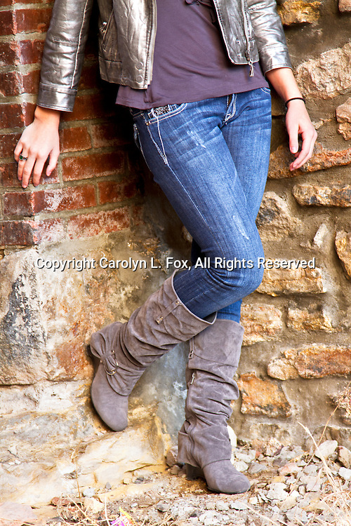 A teen-age girls leans on an old brick and stone wall in an alley in Mid-America.