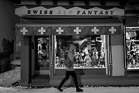 Switzerland. Canton Graubünden. Davos. Night time. A woman walks on the snowy sidewalk. The Swiss Alp Fantasy is a souvenir shop. Swiss flags on display. A gift shop or souvenir shop is a store primarily selling souvenirs, memorabilia, and other items relating to a particular topic or theme. The items sold often include  animals, toys, and other souvenirs, intended to be kept by the buyer as a memento of their visit, or given to another as a gift. Gift shops are normally found in areas visited by many tourists. The flag of Switzerland displays a white cross in the centre of a square red field. The white cross is known as the Swiss cross. 12.10.2020 © 2020 Didier Ruef