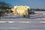beautiful yellow barn in snowy winter landscape
