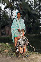 In the village of Sangrampur, a young girl carries circuit boards, which she will deliver to her family nearby who recycle e-waste as a source of income. Kolkata, India. November, 2013