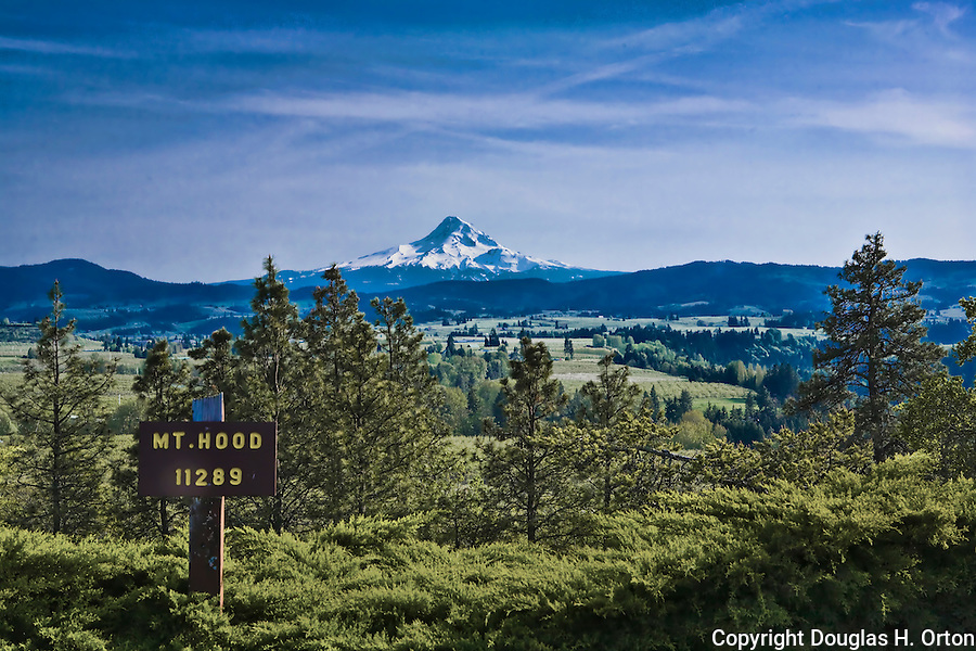 Majestic Mount Hood rises over the Hood River Valley east of the town of Hood River in the Columbia River Gorge, Oregon.  This view is from Panorama Point Park near the town of Hood River.  Hood River, east of Portland, is a favorite of wind surfers and skiers alike and is known as orchard and wine country.