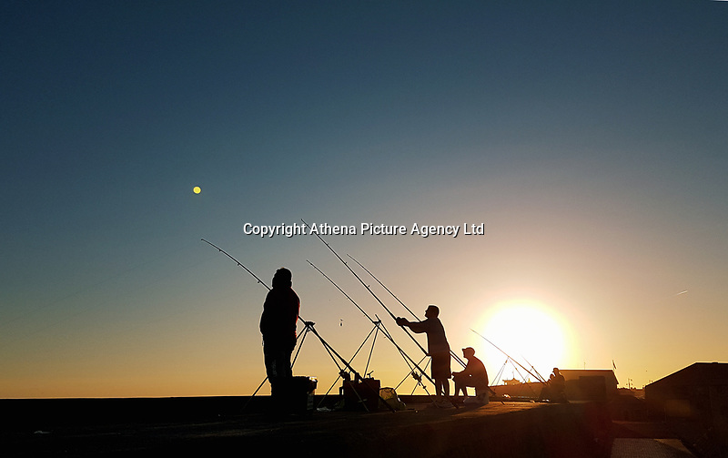 Porthcawl, UK. Saturday 17 June 2017<br /> Anglers fishing on the promenade wall near the lighthouse just before the sun sets<br /> Warm and sunny weather in most parts of the UK.