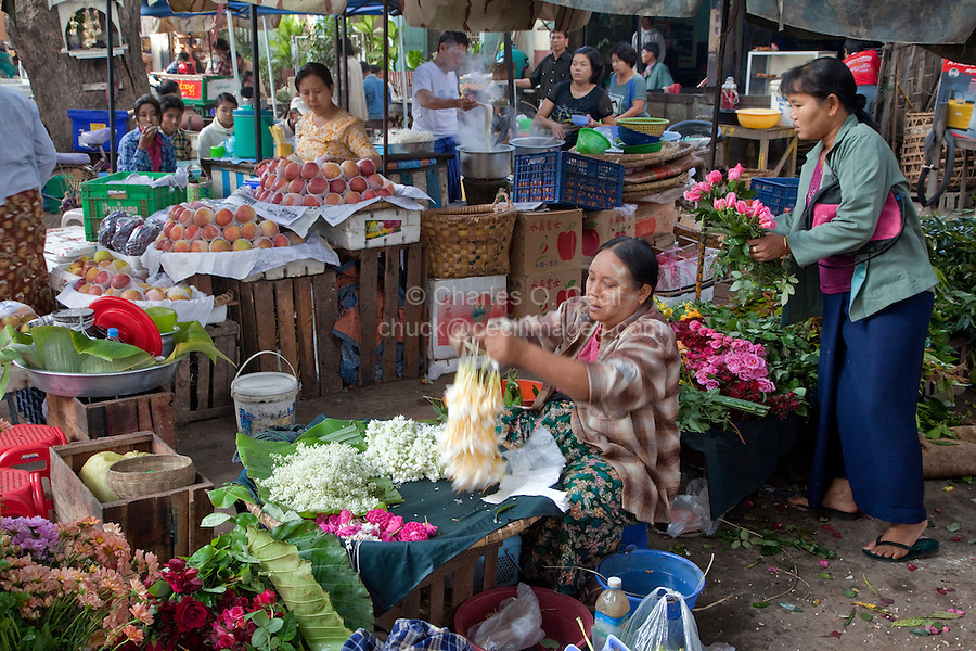 Myanmar, Burma.  Mandalay Morning Market Scene.  Apples and Flowers.