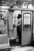 """USA. New York City. Spanish Harlem. Tito works as a car cleaner in the subway at night. Tito lives below the poverty line and receives public assistance (AFDC, Home Relief, Supplemental Security Income and Medicaid). Advertisemnt for the lottery: Lotto made our amercian dream come true"""". Spanish Harlem, also known as El Barrio and East Harlem, is a low income neighborhood in Harlem area. Spanish Harlem is one of the largest predominantly Latino communities in New York City. 25.11.86 © 1986 Didier Ruef ."""